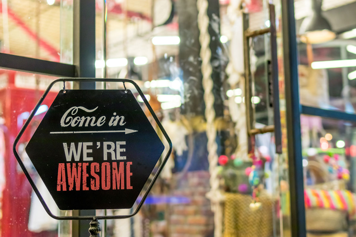 store window with a sign stating 'come in, we're awesome'